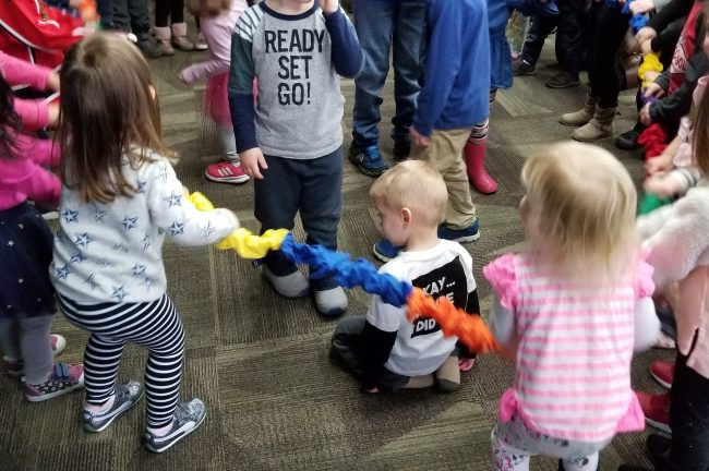 Children are gathered around a multi-colored fabric rubber band (stretchy band) and are pulling on it. Some children are in the middle of the circle.
