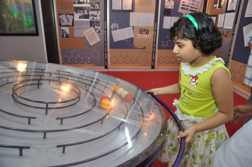 toddler interacting with science exhibit in Belgharia