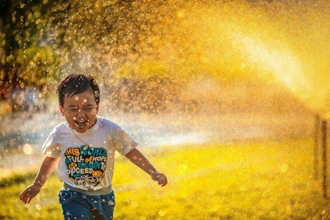 Happy child running through a sprinkler