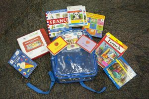 Backpack with books, flashcards, and tablet to learn French