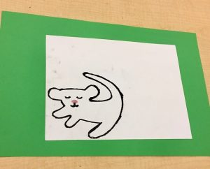 An outline of the character Simba on a white sheet of paper with a green background.