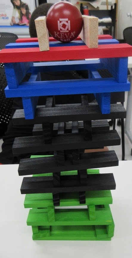 Tower made with Keva planks. A ball is centered at the top between two blocks.