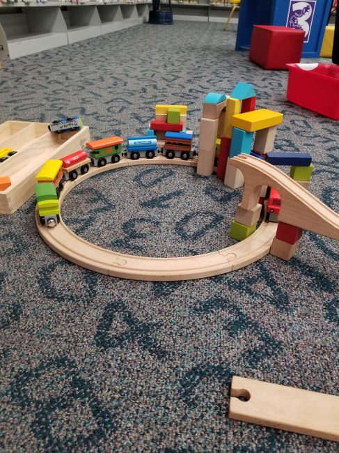Wooden toy train & tracks as part of a screen free library setting