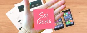 Pink Post-it Note in the left hand that states: Set Goals.