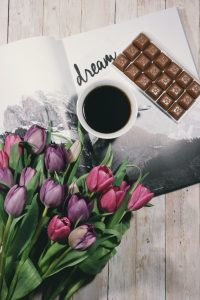 "Coffee, tulips, and a chocolate bar on top of a journal with ""Dream"" written on the page."