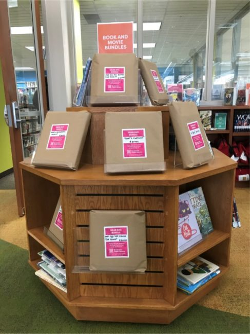 wooden book display with packages of books wrapped in brown paper