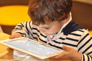 A child is staring intently at a tablet mounted on a table stand.