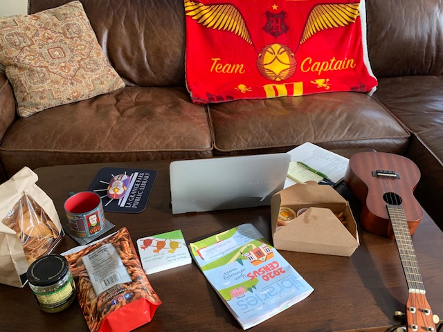 Managing from a distance often utilizes a living room office, complete with snacks and a ukuele on the coffee table