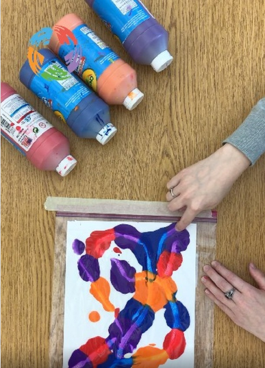 Two hands squishing paint in a bag to create mess-free art