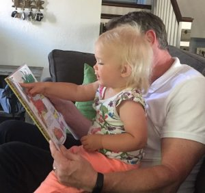 Father reads to toddler on his lap