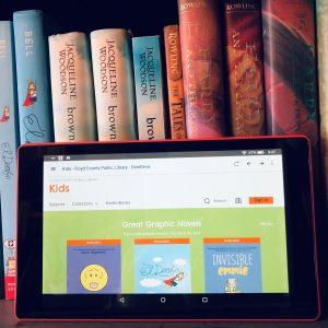 An e-reader displaying children's e-books on a shelf of books