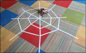 Tarantula puppet sits on a masking tape web.