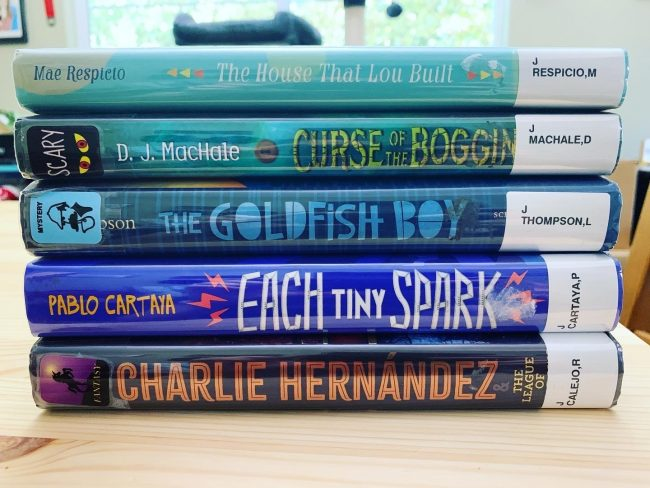 Stack of five books ready to be considered for virtual book talks
