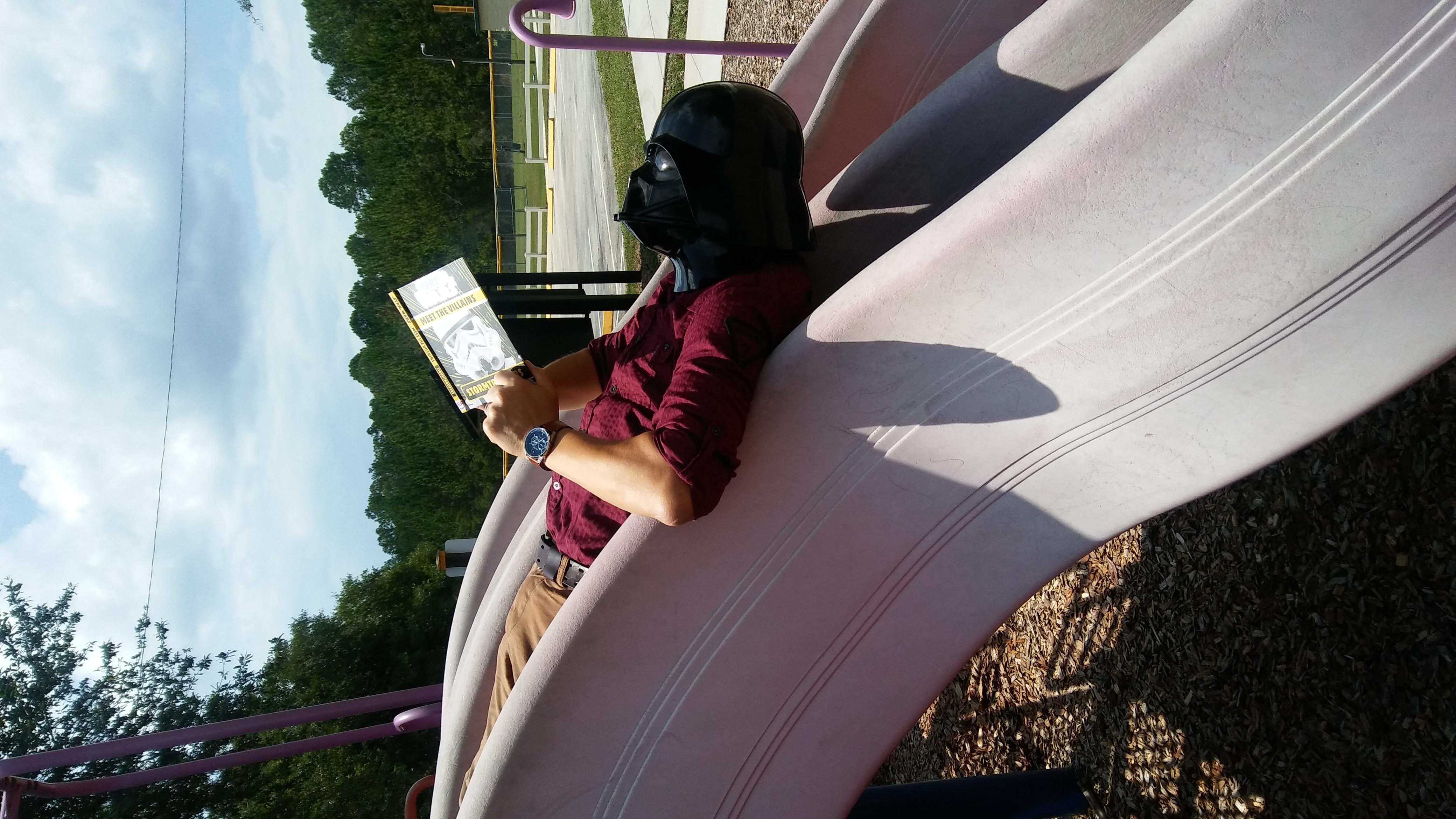 Darth Vader reading on a playground slide