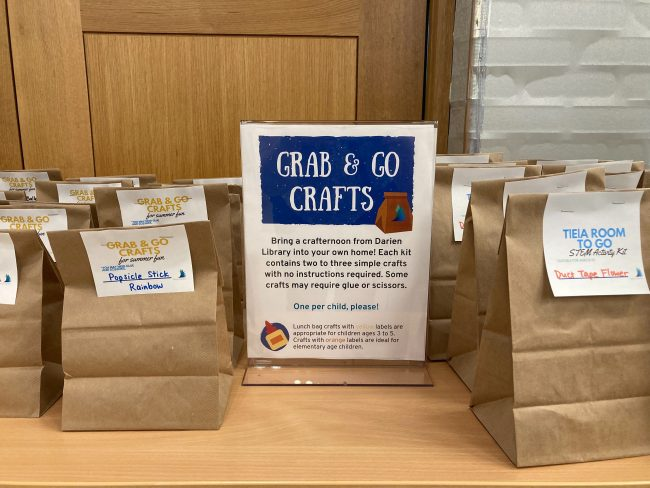 A photo of grab & go craft bag selection, featuring a sign with information for caregivers and bags full of supplies for various crafts and engineering activities.