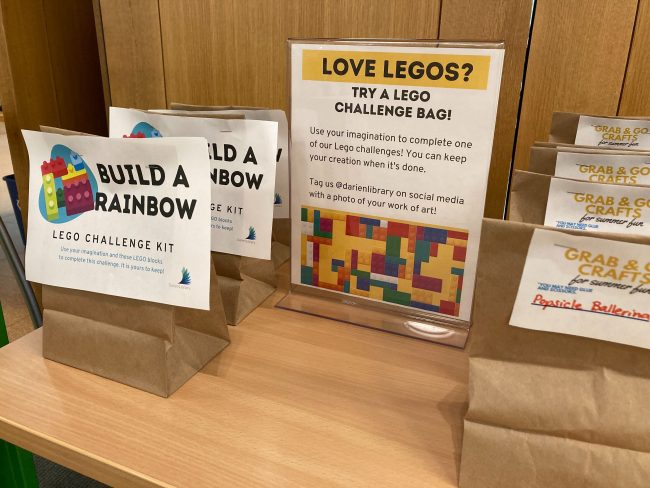 Photo features LEGO Challenge Kits and Grab & Go Craft Bags, with a sign explaining the LEGO Challenge Kits.