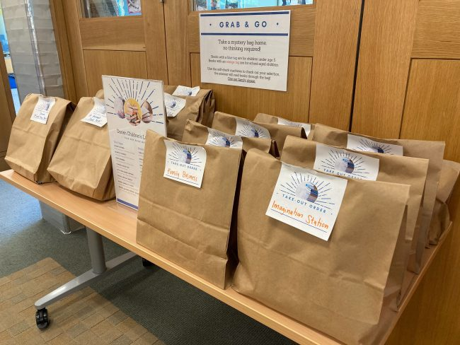 "Table covered with labelled bags. Sign above table says, ""Grab and Go: Take a mystery bag home, no thinking required."" Each bag is filled with 4-5 books on a particular theme."