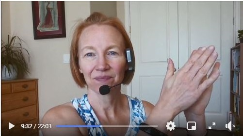A screenshot from Yoga storytime. The librarian is sitting close to the screen while wearing a headset and clapping her hands.