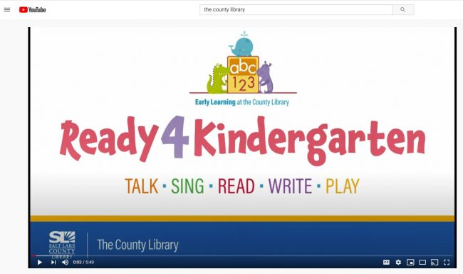 A screenshot showing the Into Image of the Ready 4 Kindergarten learning activity videos. There is a logo on top that says abc 123 and there are words under the program title that say Talk, Sing, Read, Write, Play. The footer at the bottom of the image says The County Library next to the logo for the Salt Lake County Library.