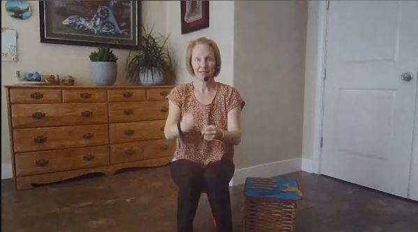 A screenshot of a librarian doing the hand movements of a song during a virtual storytime.