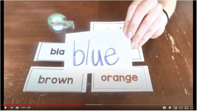Screenshot of a hand holding a handwritten card. Written on the card is word blue. Under the card you can see printed cards with other color names on them.