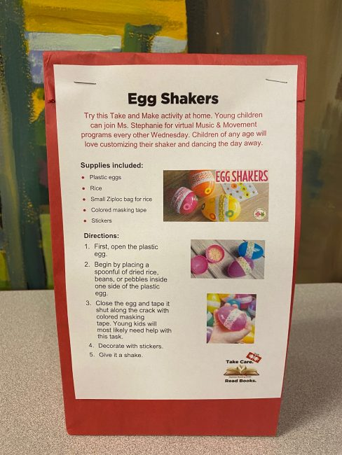 Picture of a red paper bag with instructions and supplies on how to assemble egg shakers