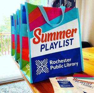 Summer Playlist bags on a table with small wax bags of sidewalk chalk with a branded sticker on the front, and Summer Playlist activity logs.