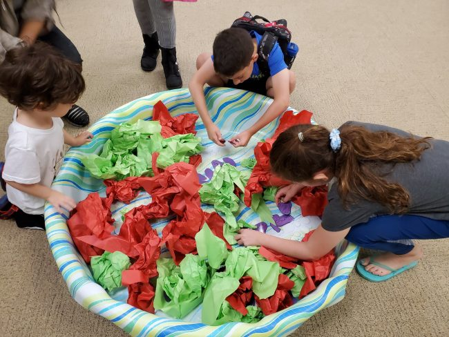 Children leaning over a kiddie pool of red and green tissue paper searching for synonyms