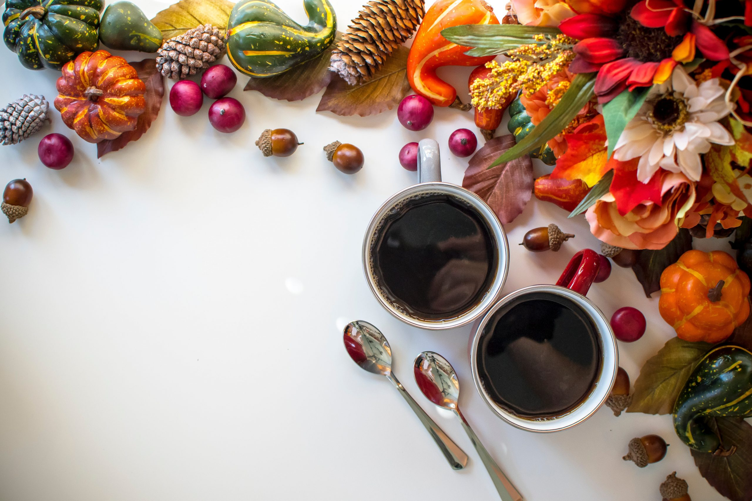 A decorative image of colorful gourds and to cups of black coffee with two spoons.