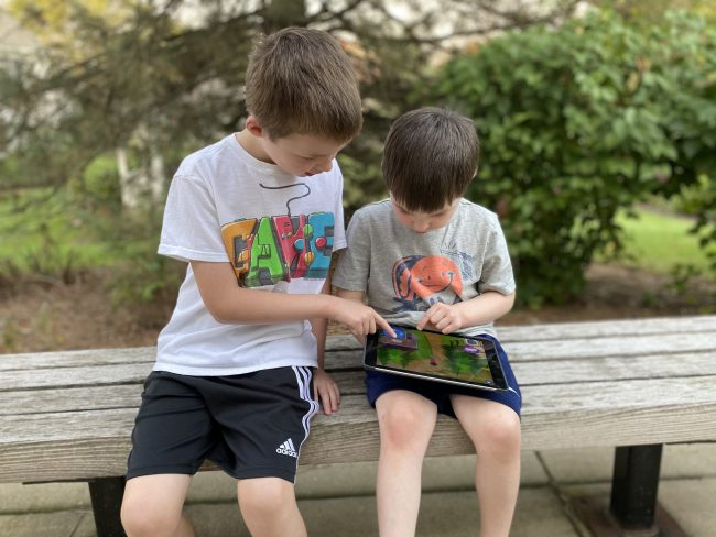Two young boys sit outside on a bench playing on a tablet computer together.