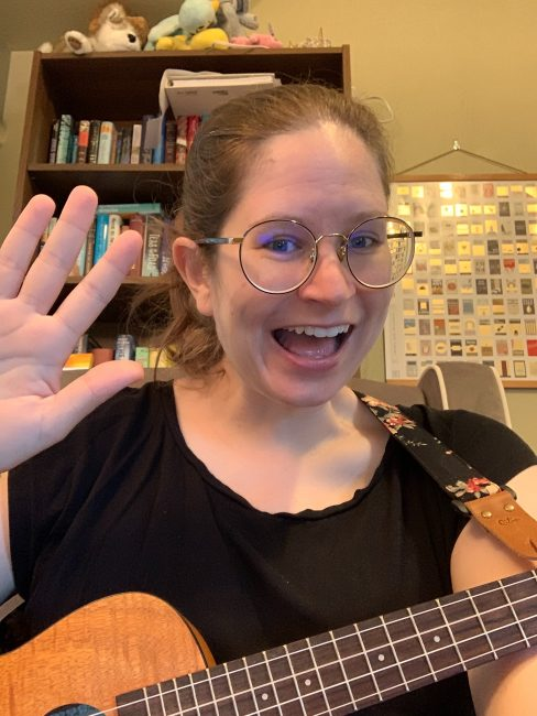 Chelsey smiling and waving at the camera with her ukulele, at the beginning of Zoom storytime.