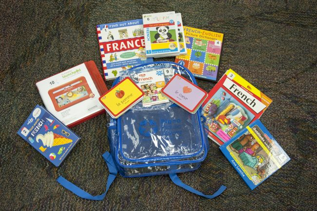 A backpack with books, flashcards, and a tablet related to learning French.