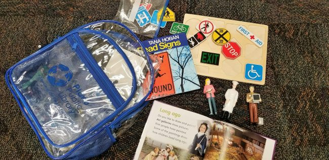 A backpack with a book, puzzle, and other children's resources.
