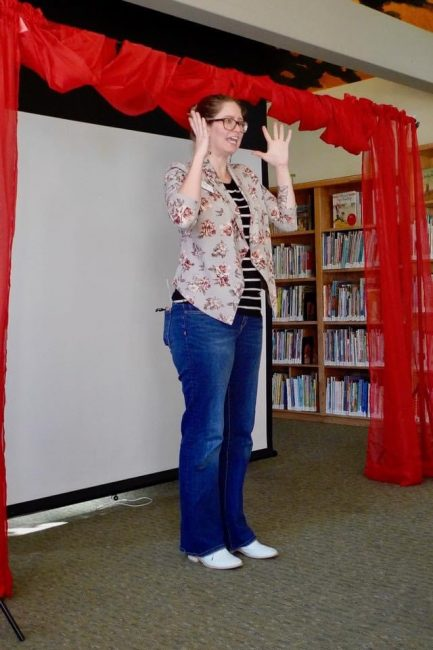Chelsey Roos stands in front of a white screen and red curtains, gesturing while telling a story.