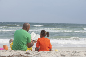 father and daughter reading a book together at the beach