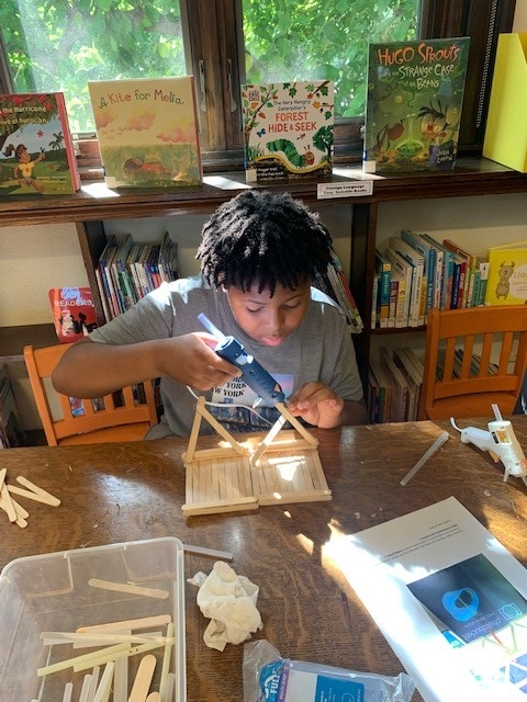 Child using hot glue to make the base for a bridge