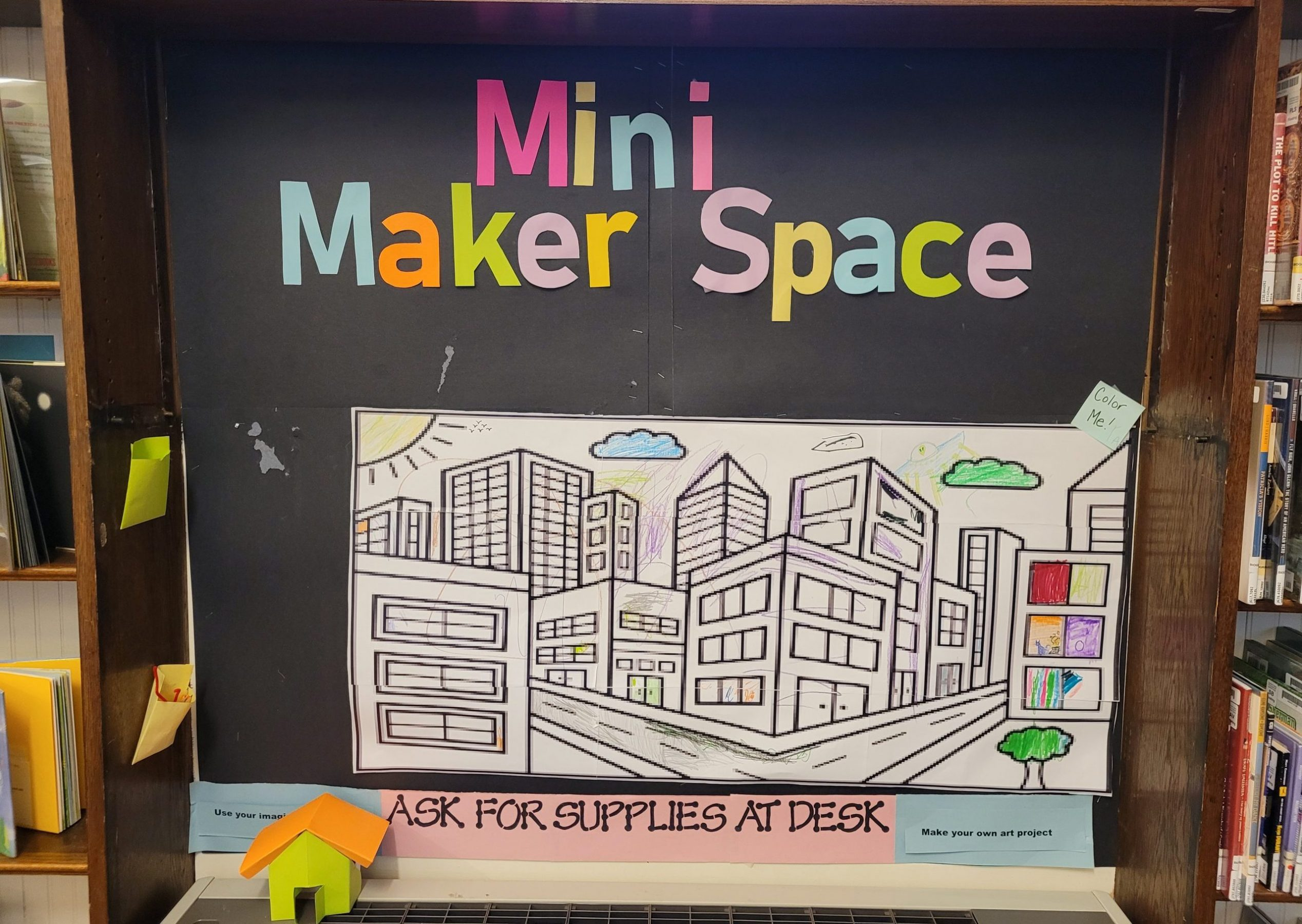 """Image of display with a black background, """"MIni Makerspace"""" in bright colors with a giant coloring page attached"""